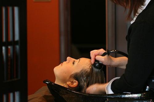 jeune fille au bac se faisant laver les cheveux