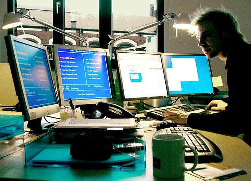Homme travaillant sur plusieurs ordinateurs