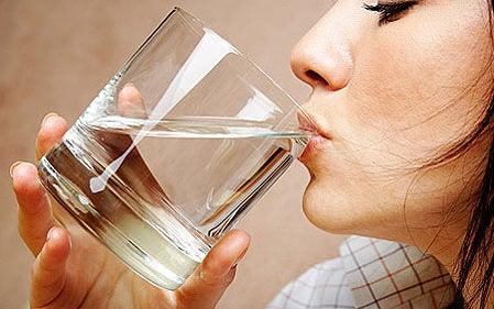 femme buvant de l'eau pour éliminer les ballonnements