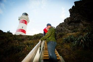 Un père qui monte les escalier d'un phare