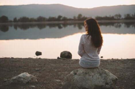 Femme assise près d'un lac