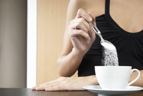 Femme qui verse du sucre dans son café