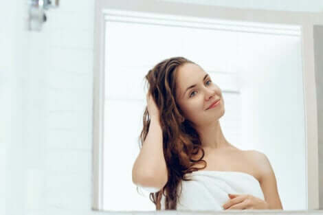 une femme qui sort de la douche devant un miroir.