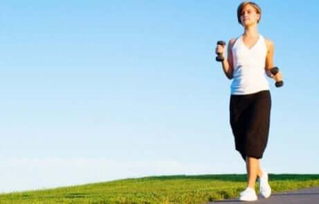 Une femme qui marche avec des haltères.