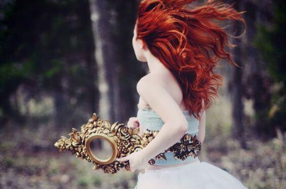 Femme rousse avec miroir dans la main