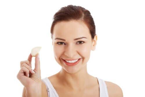 Une femme avec une gousse d'ail dans la main.