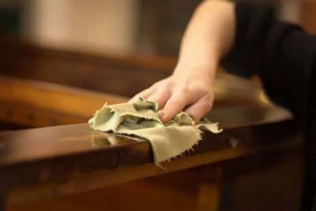 Femme en train de nettoyer un meuble en bois