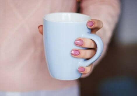 Une femme qui tient une tasse dans sa main