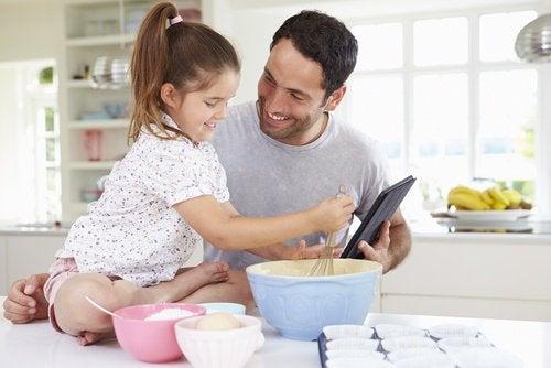 Homme qui cuisine avec sa petite fille dans ses bras et importance à 60 ans