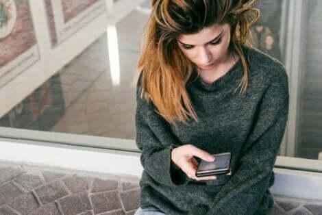 Une femme inquiète qui regarde son téléphone.