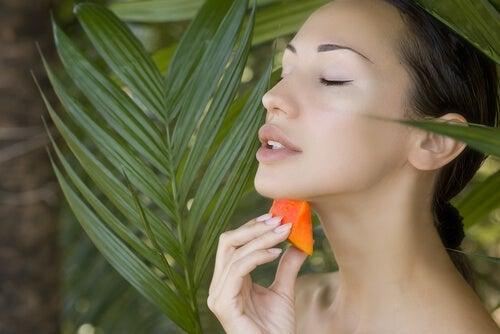 Femme qui applique de la papaye sur le visage