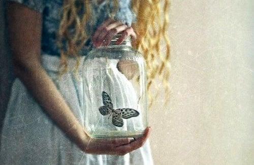 femme portant un vase de crystal avec un papillon