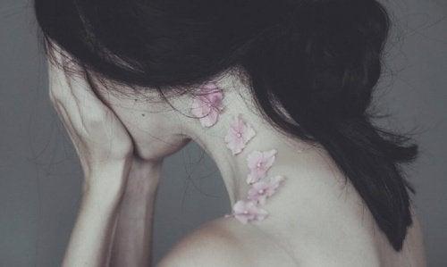 Femme en souffrance, se cache le visage.