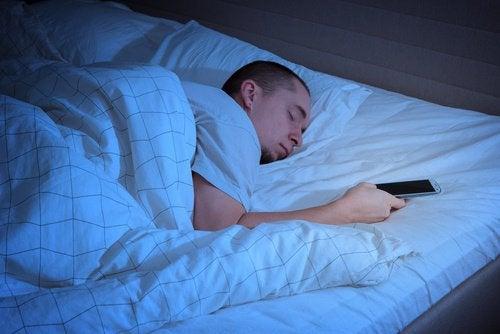 homme avec son portable au lit