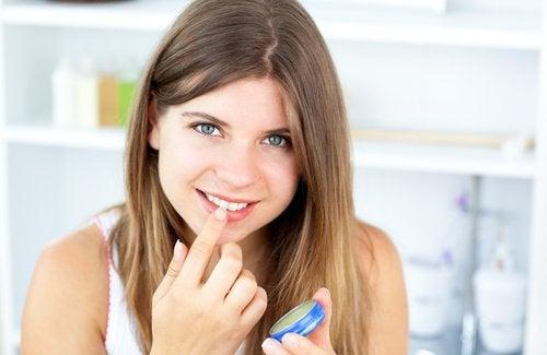 Femme appliquant d la vaseline sur ses lèvres