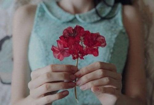 l'humilité - photo d'une jeune fille tenant une fleur rouge