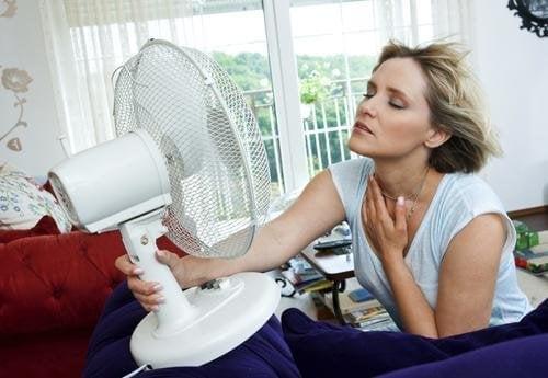 femme qui a la ménopause souffrant de bouffées de chaleur