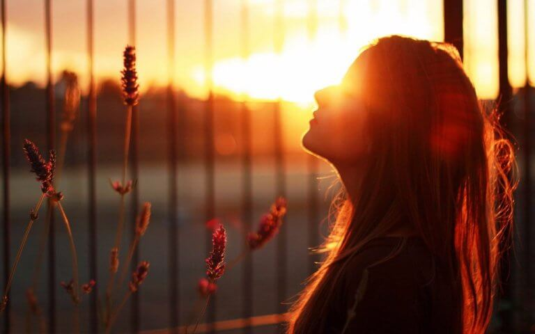 femme devant le soleil qui se couche