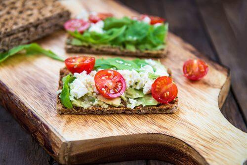 crackers aux graines agrémentés de tomates, de salade et de fromage frais