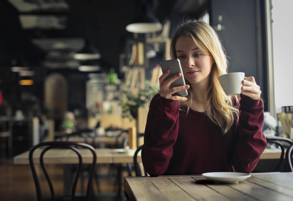 femme buvant un café en regardant son téléphone portable