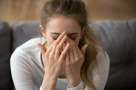 femme portant ses mains à son visage