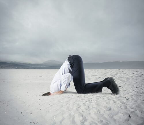 homme enfouissant sa tête dans le sable