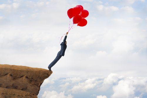 homme au bord d'une falaise accroché à des ballons