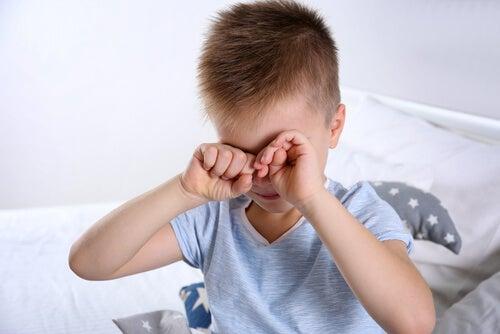 enfant se frottant les yeux