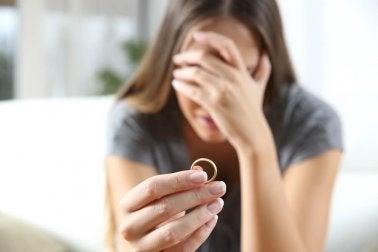 Femme triste avec une alliance entre les doigts