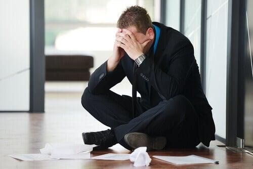 homme stressé assis par terre