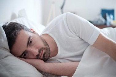homme triste dans son lit