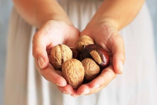 Une femme tient des noix dans sa main