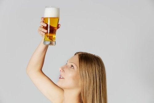 Femme qui tient un verre de bière pour la chevelure