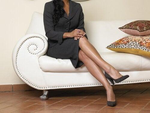 femme assise sur le canapé avec les jambes croisées