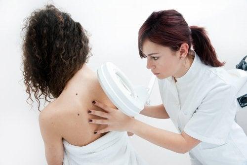 Dermatologue qui analyse le grain de beauté suspect d'une patiente