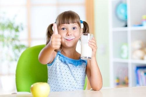 Petite fille qui boit un verre de lait
