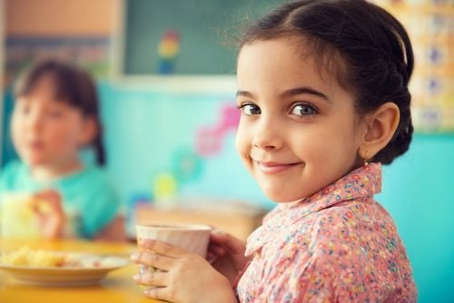 Petite fille avec une tasse à la main