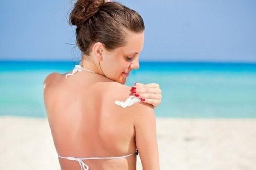 Femme qui met de la crème solaire