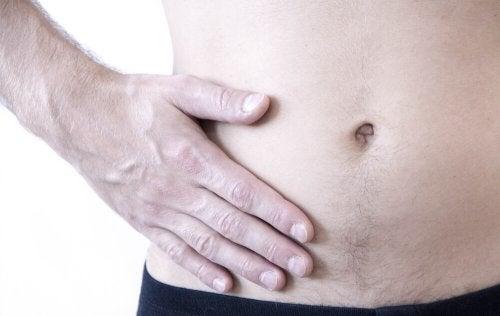 Gros plan sur le ventre d'une homme avec la main droite posée sur la partie droite de l'abdomen