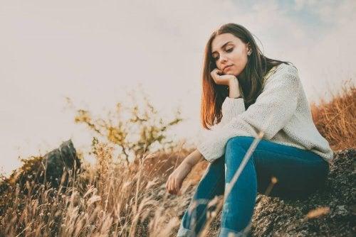 Femme assise dans un champ contrôler l'anxiété