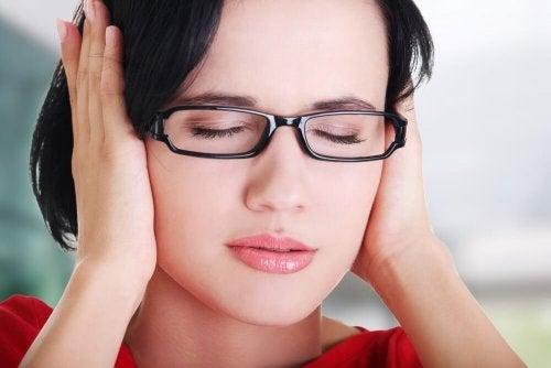 Femme avec ses mains sur les oreilles
