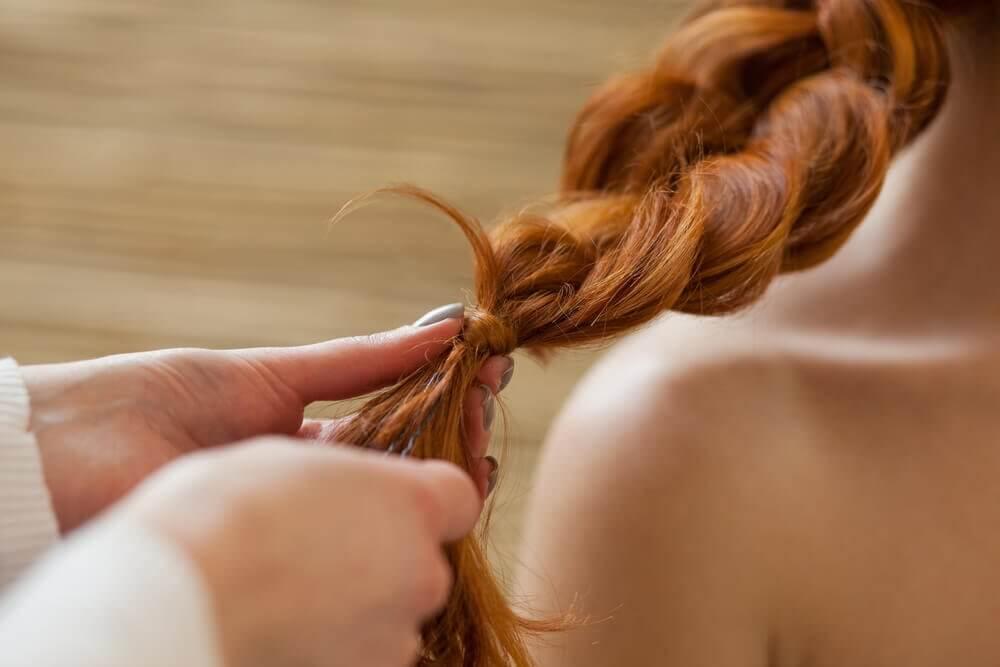 femme faisant une natte pour des cheveux longs et sains