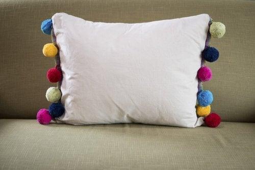 Des coussins avec des pompons en laine