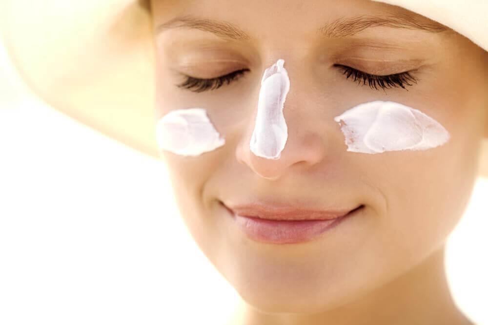 Crème solaire sur le visage d'une femme