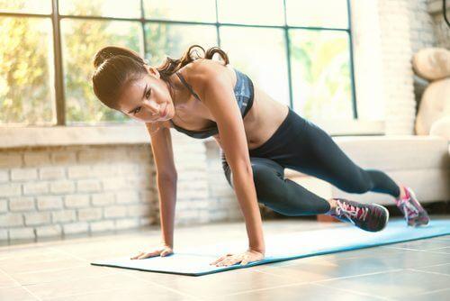 une jeune femme fait des exercice au sol lors de sa séance d'entraînement