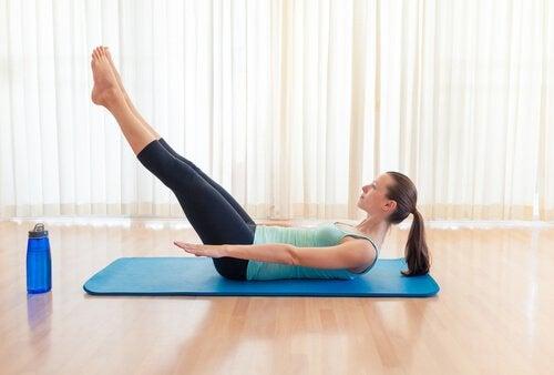 une femme fait des exercice d'abdominaux au sol pour avoir des fesses toniques