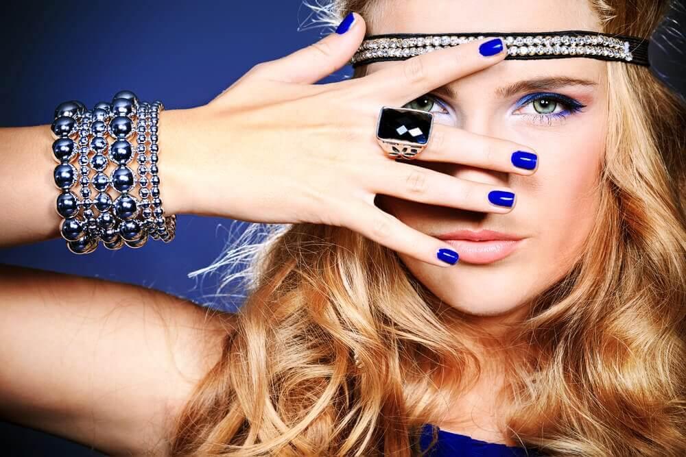 Une femme pose sur fond bleu avec beaucoup de bracelets