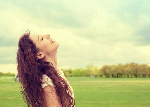 Femme qui sourit le visage tourné vers le ciel