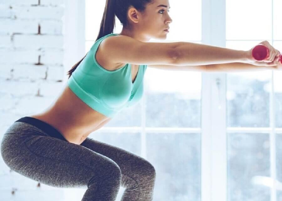 une femme fait des squats avec un haltère entre les mains pour avoir des fesses toniques