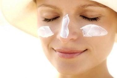 Femme qui applique de la crème solaire pour hydrater sa peau